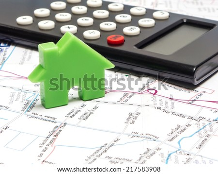 Green house and calculator on the map , property concept - stock photo