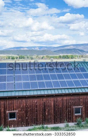 green house powered by solar panels in the mountains - stock photo