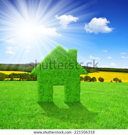 Green house symbol on meadow with sunny sky - stock photo