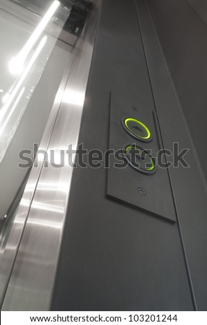 green illuminated elevator buttons and glass and aluminium door opening - stock photo