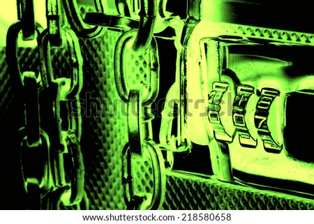 Green image of metallic suitcase with safety code and chains around it - stock photo