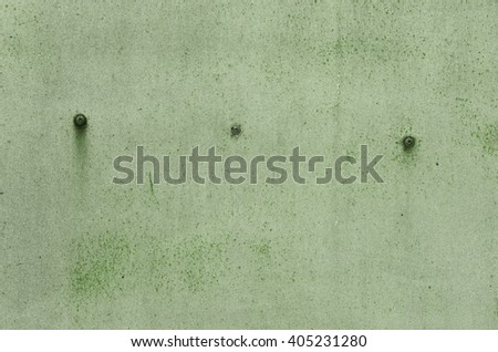 Green iron wall with old paint with streaks of rust and rusty screws. textural composition
