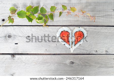 Green ivy vine and two pieces of sushi forming a heart shape on a vintage wooden table - stock photo