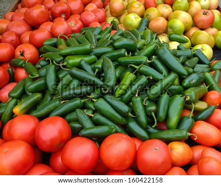 Green Jalapenos and Red Tomatoes at the Market - stock photo