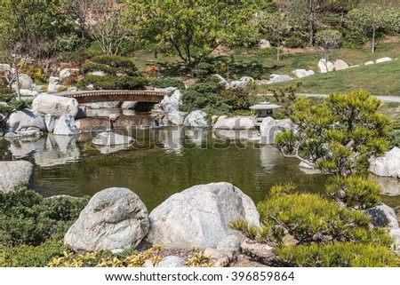 Green Japanese garden. Trees, shrubbery, rocks, and a small bridge over the pond  - stock photo