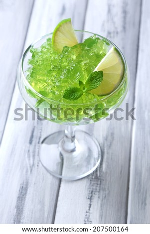 Green jelly with mint leaves in glass on wooden background - stock photo
