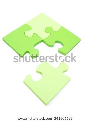 Green  jigsaw puzzle with piece off on white background