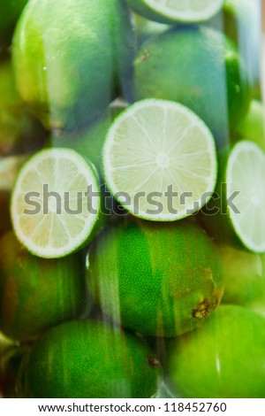 Green juicy limes in the big glass of cold water
