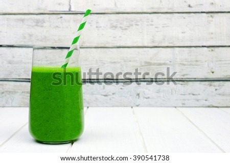 Green kale smoothie in a glass with straw on a rustic white wood background - stock photo