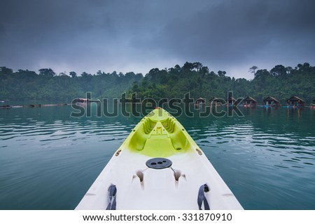 Green Kayak on Morning after rain in a lake forest and river natural attractions in Thailand. - stock photo