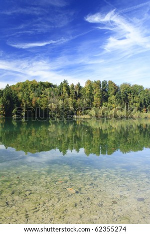 green lake with colorful wood and blue sky in autumn - stock photo
