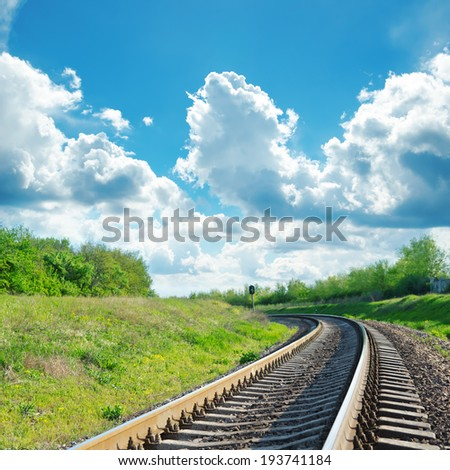 green landscape with railroad to horizon and blue sky with clouds over it - stock photo