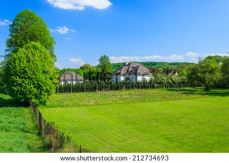 Green lawn and houses in countryside landscape of Poland near Krakow town on sunny summer day
