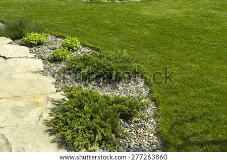 Green lawn in a colorful landscaped formal garden.Detail of a botanical garden - stock photo