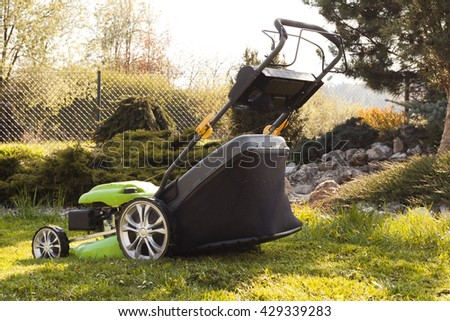 Green lawn mower in the summer garden