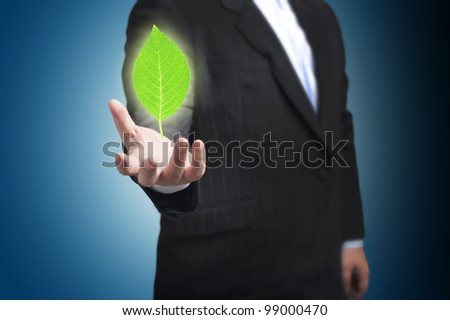Green Leaf floating on the businessman's hand. Concept for environmental conservation - stock photo