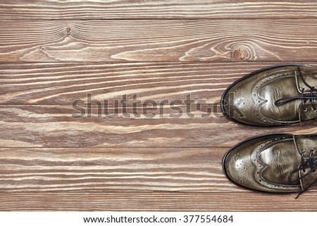 Green leather men's shoes on wooden background