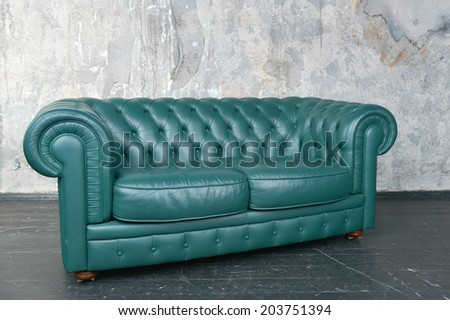 Green leather sofa in a shabby room - stock photo