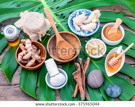 Green leaves with nature spa ingredient turmeric powder in white mortar ,ginger,herbal compress ball,honey,soap,cinnamon powder ,cinnamon sticks, tamarind,wooden bowl ,wooden spoon and sea salt. - stock photo