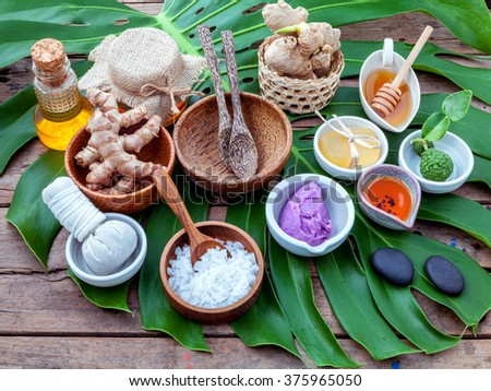 Green leaves with nature spa ingredient turmeric powder in white mortar ,ginger,herbal compress ball,honey,soap ,lavender scrub,cinnamon powder ,wooden bowl ,wooden spoon and sea salt.