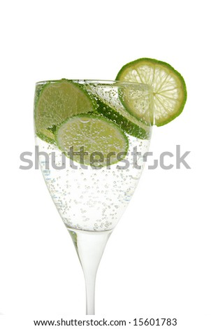 Green lemon in the glass with water. On the white background