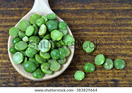 Green lentil beans in wooden spoon on wooden background, top view - stock photo