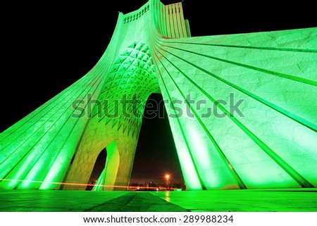 Green lights of popular Azadi (Liberty) Tower at night in Tehran. One of the symbols of Tehran city, the capital of Iran, and marks the west entrance to the city. - stock photo