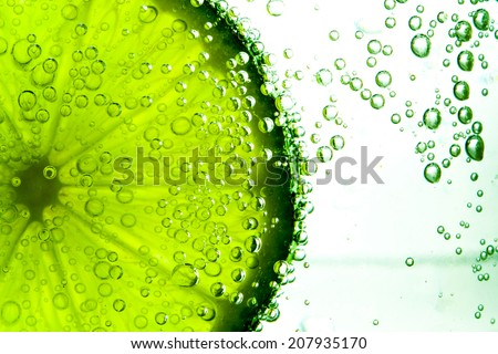Green lime with water splash isolated on white background - stock photo