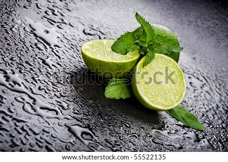Green limes with mint and water drops on black background - stock photo
