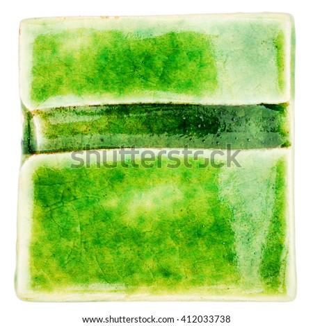 Green lined handmade glazed ceramic tile isolated on white background - stock photo