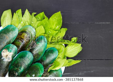 Green-lipped mussels with Basil on black wooden background - stock photo