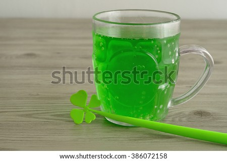 Green liquid in a beer mug displayed with a four leaf clover for St. Patrick's day - stock photo