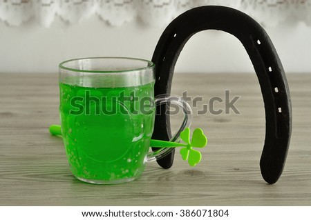 Green liquid in a beer mug displayed with a horseshoe and a four leaf clover for St. Patrick's day - stock photo