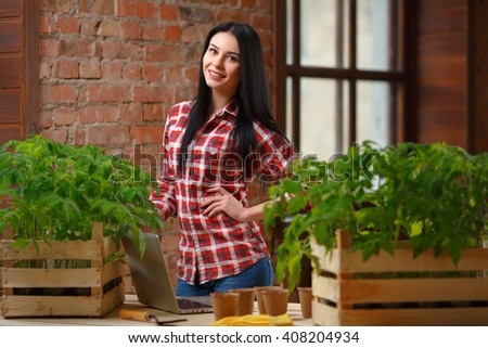 Green living. Shot of an attractive female gardener standing with a laptop looking to the camera cheerfully posing in her personal greenhouse.