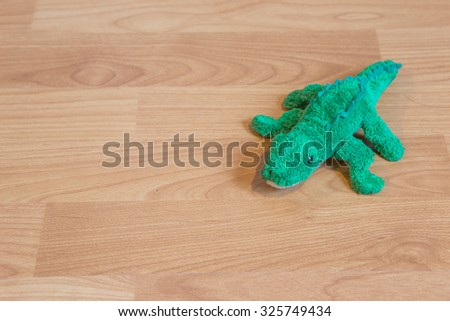 Green lizard plush toy on wooden floor.