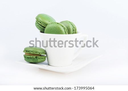 green macaroon in a white coffee cup on a white background - stock photo
