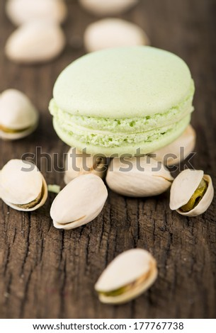 Green macaroons with pistachio over wooden background