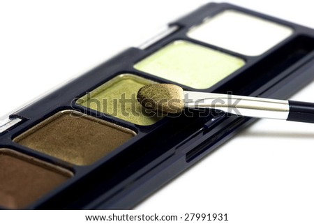 green make-up eyeshadows and cosmetic brush - stock photo
