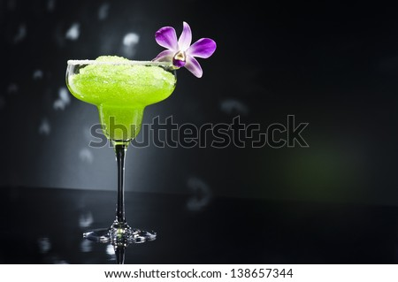 Green margarita cocktail with orchid flower - stock photo