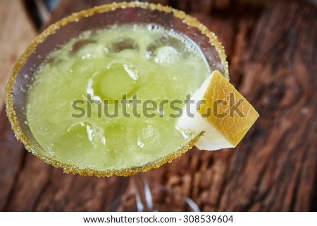 Green margarita melon cocktail with copy space on wooden background. - stock photo