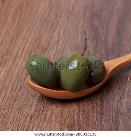green marinated olives over wooden background