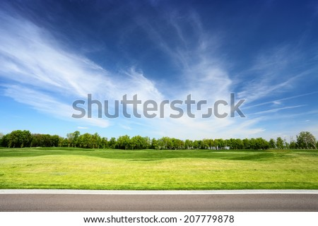 Green meadow and blue sky with asphalt road on foreground. Landscape in summer sunny day.