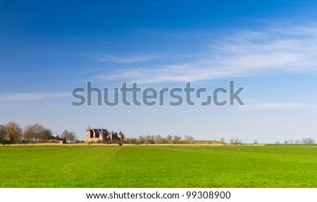 Green meadow, blue sky, castle on the horizon - stock photo