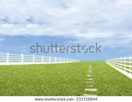 Green meadow blue sky with white fence. - stock photo