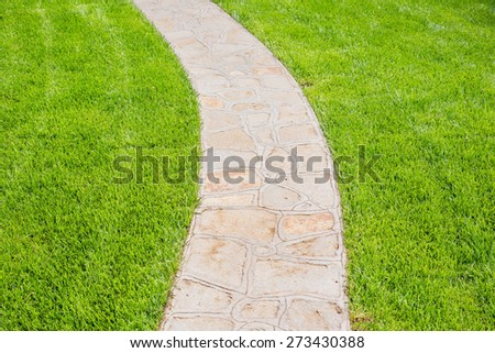 Green meadow divided by rough stone walkway, focus is on the center