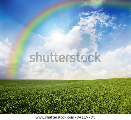 Green meadow under blue sky with a rainbow - stock photo