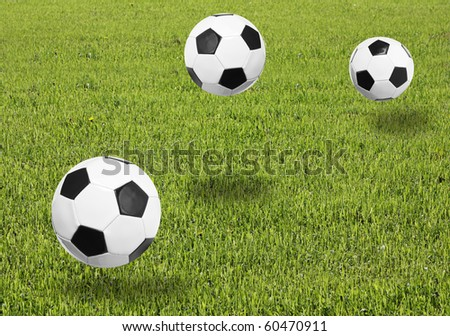 Green meadow with a soccer balls on it. - stock photo