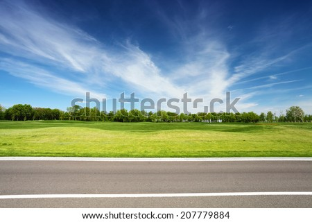 green meadow with trees and asphalt road, blue sky on background - stock photo