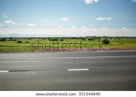 green meadow with trees and asphalt road, blue  skyand field  on background - stock photo