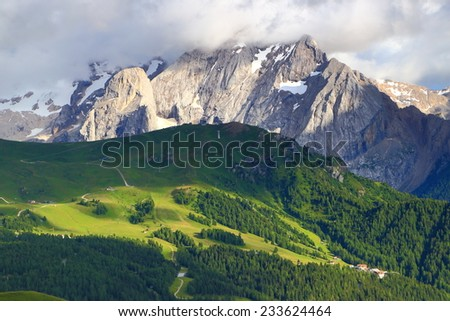 Green meadows and cloudy summits seen from Sella pass, Dolomite Alps, Italy - stock photo
